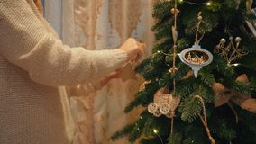 Beautiful blonde girl dresses up a Christmas tree in a cozy evening house stock video
