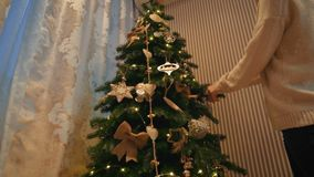Beautiful blonde girl dresses up a Christmas tree in a cozy evening house stock video footage