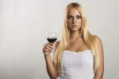 Beautiful blond girl with wineglass.dry red wine.sexy young woman with alcohol. your text here. Beautiful blond girl with wineglass.girl in blue dress.dry red Stock Photos