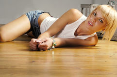 Beautiful blond girl on wooden floor Royalty Free Stock Photography