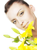 Beautiful blond girl with yellow lily Royalty Free Stock Images