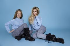 Beautiful blond girls, mother with daughter in autumn winter clothing on a blue background in the studio stock photo