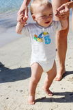 Beautiful blond hair blue eyes baby moving first steps on the beach.  Stock Photo
