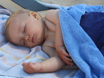 Beautiful blond hair blue eyes baby sleeping on the beach.  Royalty Free Stock Photo