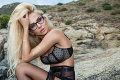 Beautiful blond hair sexy woman young girl model in sunglasses and elegant black swimsuit Royalty Free Stock Images