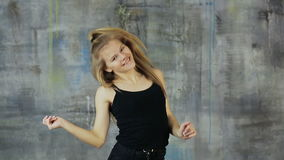 Beautiful blond hair teen girl dancing hiphop on the gray wall. Actively works with hands. stock footage