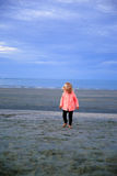 Beautiful blond-haired girl walking on sand beach at the Sunrise Stock Image