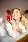 Beautiful blond happy smiling young woman in bed looking up Royalty Free Stock Image