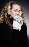 Beautiful blond in headphones and mittens Royalty Free Stock Photo