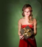 Beautiful blond holding gift box. Half length portrait of beautiful blond holding gift box with creative lighting Stock Photo