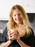 Beautiful blond holding a large coffee Stock Photography