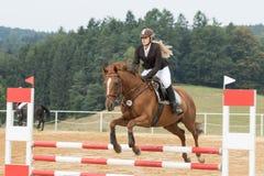 Beautiful blond horsewoman jumping Stock Photos