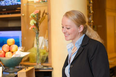 Beautiful blond hotel receptionist Stock Photo
