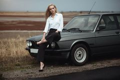 Beautiful blond lady in black striped high waisted pants, white blouse and high heeled shoes sitting on the hood of her old car royalty free stock photography