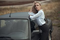 Beautiful blond lady in black striped high waisted pants and white blouse leaning on the top of her old car. The wind in her hair. Rain drops on the roof of stock image