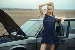 Beautiful blond lady in luxurious dark blue sequin tassel evening dress standing at her old car with open hood. Leaning on its door. Empty field around. Outdoor stock photos