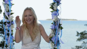 Beautiful blond lady on swing near sea. stock video