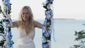 Beautiful blond lady on swing near sea. stock video footage