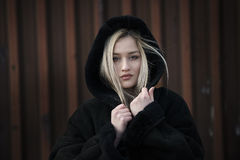 Beautiful blond lady wear hooded black jacket. Beautiful blond lady with long hair and big reb lips wear womens hooded jacket. Facing the camera with her pretty royalty free stock photo