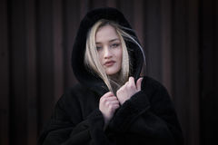 Beautiful blond lady wear hooded black jacket. Beautiful blond lady with long hair and big reb lips wear womens hooded jacket. Facing the camera with her pretty royalty free stock photos