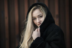Beautiful blond lady wear hooded black jacket. Beautiful blond lady with long hair and big reb lips wear womens hooded jacket. Facing the camera with her pretty stock photo