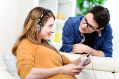 Beautiful blond listening to music while her boyfriend watching Royalty Free Stock Photos