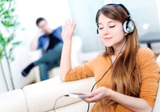 Beautiful blond listening to some music while her boyfriend is b Royalty Free Stock Photos