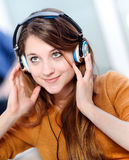 Beautiful blond listening to some music while her boyfriend is b Stock Image