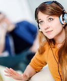 Beautiful blond listening to some music while her boyfriend is b Stock Photos