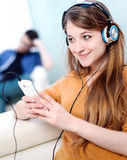Beautiful blond listening to some music while her boyfriend is b Royalty Free Stock Images