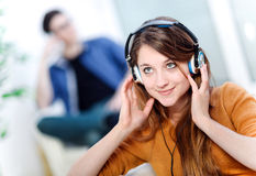 Beautiful Blond Listening To Some Music While Her Boyfriend Is B Stock Photography