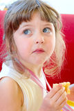 Beautiful blond little dizzy concerned that called and reprimanded while chewing a piece of cake at a birthday party. Royalty Free Stock Images
