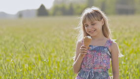 Beautiful blond little girl eats ice-cream in the summer next to the wheat field. Warm sunny day. stock video footage