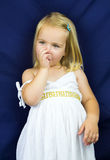 Beautiful blond little girl holding a finger in her mouth Royalty Free Stock Photo