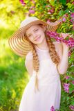 Beautiful blond little girl with long hair in the spring park. Near the bushes of blossoming purple lilacs Royalty Free Stock Photos