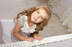 Beautiful blond little girl near a piano Royalty Free Stock Images