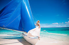 Beautiful blond long hair bride in long white open back dress with pearls. She stay on the blue sailboat. Blue sky and  turquoise Stock Image