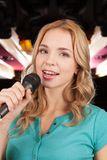Beautiful blond with microphone standing and singing. Royalty Free Stock Photography