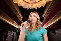 Beautiful blond with microphone standing and singing. Stock Photos