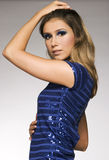 Beautiful blond model. In blue lucid dress posing on grey background stock photography