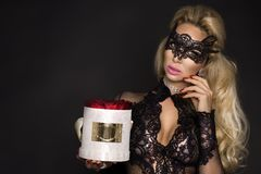 Beautiful blond model in elegant dress holding a gift, flower box with roses. Valentine`s gift royalty free stock image