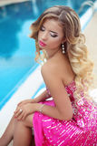 Beautiful blond model girl in fashion pink dress with makeup and Royalty Free Stock Photos