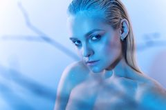 Beautiful blond model with nude make up, slicked back hair and naked shoulders in blue light Stock Photos