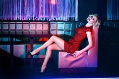 Beautiful blond model in red short fitted sequin dress relaxing on the square sofa in night club. Beautiful blond model with provocative make up wearing red royalty free stock photography