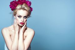 Beautiful blond model with updo hair blown by the wind and perfect make up wearing peony head garland Stock Images
