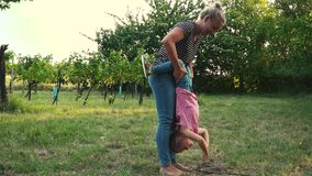 Mother and daughter playing outdoor. Beautiful blond mother and her cute daughter are playing outdoor and having a lot of fun