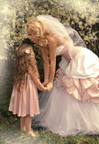 A beautiful blond mother with a small daughter girl snuggling on nature background of green and purple flowers Royalty Free Stock Images