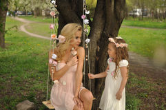 A beautiful blond mother with a small daughter girl snuggling on nature background of green and purple flowers and colorful soap b Royalty Free Stock Photos