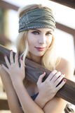 Beautiful blond with olive green headband sitting on wooden pier in St.Augustine, Florida. Royalty Free Stock Photos