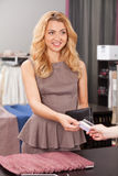 Beautiful blond paying in store with card. Attractive lady buying tissue in store royalty free stock photo